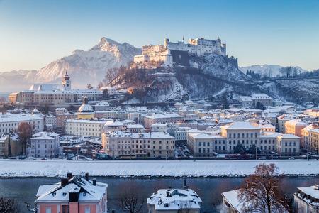 冬、ザルツブルク、オーストリアの美しい寒い晴れた日に風光明媚な朝の日の出の光で有名なホーエン ザルツブルク城塞など、ザルツァッハ川の歴