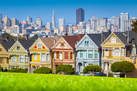 Classic postcard view of famous Painted Ladies, a row of colorful Victorian houses located at scenic Alamo Square, with the skyline of San Francisco in the background on a beautiful sunny day with blue sky in summer Archivio Fotografico