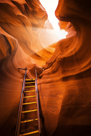 lake powell: Beautiful view of amazing sandstone formations with a ladder leading toward a magic light beam in famous Antelope Canyon near the historic town of Page at Lake Powell, American Southwest, Arizona, USA Stock Photo