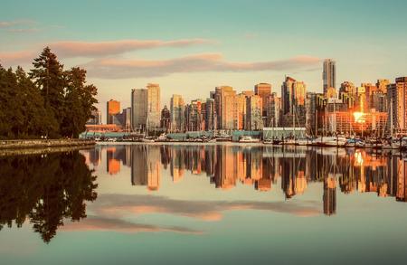日没、ブリティッシュ コロンビア州、カナダでスタンレー パークとバンクーバーのスカイラインの美しい景色 写真素材
