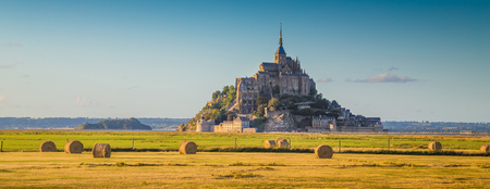 mount saint michael: Beautiful view of famous historic Le Mont Saint-Michel in golden evening light at sunset in summer with hay bales on fields with retro vintage  style pastel filter effect Normandy France