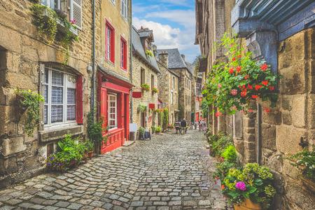Hermosa vista del pintoresco callejón estrecho con casas tradicionales históricos y de la calle de adoquines en una antigua ciudad en Europa con el cielo azul y las nubes en verano con efecto de filtro de época grunge retro
