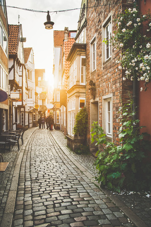 Beautiful view of old town in Europe in beautiful golden evening light at sunset in summer with pastel toned retro vintage  style grunge filter and lens flare sunlight effect