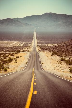 Klassieke panorama van een eindeloze rechte weg die door het kale landschap van het Amerikaanse zuidwesten met extreme hitte nevel op een mooie warme zonnige dag met blauwe hemel in de zomer Stockfoto