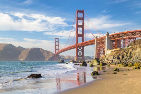 Classica vista panoramica del famoso Golden Gate Bridge visto da scenico Baker Beach nella bella luce dorata serata in una giornata di sole con cielo azzurro e nuvole in estate, San Francisco, California, USA