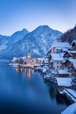 Classic postcard view of famous Hallstatt lakeside town in the Alps with beautiful Hallstattersee in mystical post sunset twilight during blue hour at dusk in winter, Salzkammergut, Austria