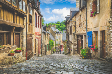 Beautiful view of scenic narrow alley with historic traditional houses and cobbled street in an old town in Europe with blue sky and clouds in summer with retro vintage Instagram grunge filter effect 스톡 콘텐츠