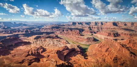 Aerial panoramic view of scenic Dead Horse Point State Park with famous Colorado river flowing on a beautiful sunny day with blue sky and dramatic clouds in summer, Utah, American Southwest, USA