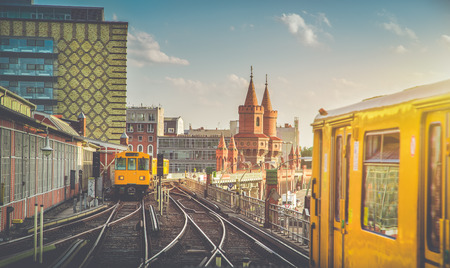 Panoramic view of Berliner U-Bahn with Oberbaum Bridge in the background in golden evening light at sunset with retro vintage Instagram style hipster filter effect, Berlin Friedrichshain-Kreuzberg 版權商用圖片 - 73490078