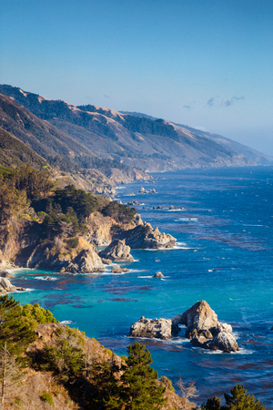 Scenic view of the rugged coastline of Big Sur with Santa Lucia Mountains along famous Highway 1 illuminated in beautiful golden evening light at sunset in summer, California Central Coast, USA 版權商用圖片