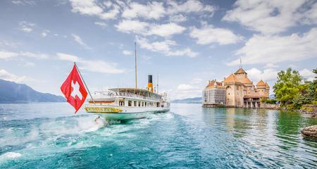 Toneelpanorama van het traditionele schip van de peddelstoombootexcursie met historische Chateau DE Chillon bij beroemd Meer Genève op een zonnige dag met blauwe hemel en wolken in de zomer, kanton van Vaud, Zwitserland Stockfoto