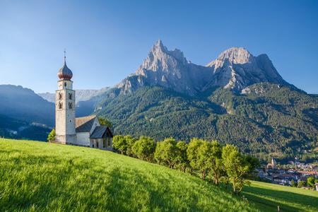 Vista panoramica del paesaggio montano idilliaco nelle Dolomiti con la chiesa di San Valentin e il famoso monte Sciliar in bella luce del mattino all'alba, villaggio di Seis am Schlern, Alto Adige, Italia Archivio Fotografico - 74674872