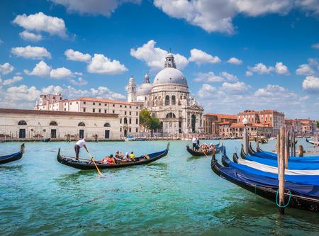 Beautiful view of traditional Gondolas on Canal Grande with historic Basilica di Santa Maria della Salute in the background on a sunny day in Venice, Italy Stock Photo