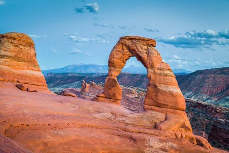 Classic postcard view of famous Delicate Arch, symbol of Utah and a popular scenic tourist attraction, in beautiful post sunset twilight at dusk in summer, Arches National Park, Moab, Utah, USA