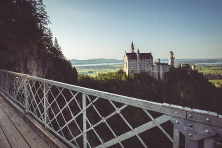 allgau: Beautiful view of world-famous Neuschwanstein Castle, the 19th century Romanesque Revival palace built for King Ludwig II, in evening light at sunset seen from Marienbrucke, Allgau, Bavaria, Germany
