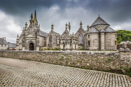 Classic panoramic view of famous ancient Parish Church of Saint Miliau with dark dramatic clouds in summer in the commune of Guimiliau, arrondissement of Morlaix in Brittany, northwestern France