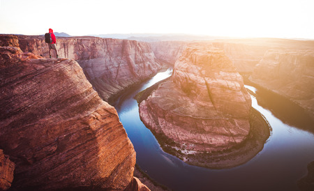 A male hiker is standing on steep cliffs enjoying the beautiful view of Colorado river flowing at famous Horseshoe Bend overlook in beautiful golden evening light at sunset in summer, Arizona, USA Stock Photo