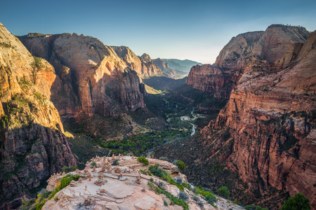 Panoramic view of Zion Canyon from the top of Angels Landing in beautiful golden evening light at sunset on a sunny day with blue sky in summer, Zion National Park, Springdale, southwestern Utah, USA