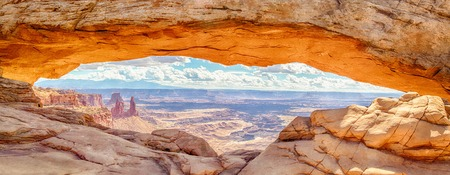 Panoramic view of famous Mesa Arch, iconic symbol of the American West, illuminated golden in beautiful morning light on a sunny day with blue sky and clouds, Canyonlands National Park, Utah, USA Фото со стока
