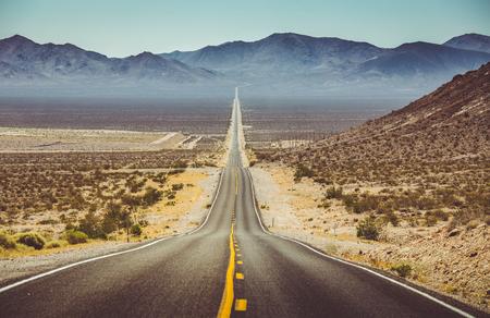 Klassische Panoramablick auf eine endlose gerade Straße, die durch die kargen Landschaft des amerikanischen Südwestens mit extremer Hitze Dunst an einem schönen heißen sonnigen Tag mit blauem Himmel im Sommer läuft Standard-Bild