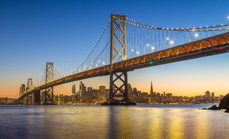 Classic panoramic view of famous Oakland Bay Bridge with the skyline of San Francisco illuminated in beautiful twilight after sunset in summer, California, USA