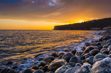 Panorama view of amazing ocean scenery with rocks on a beach in beautiful golden evening light at sunset with blue sky, clouds and sunlight lens flare effect in the background in summer