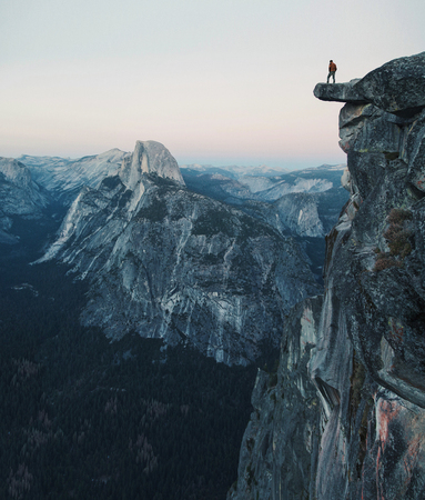 A fearless hiker is standing on an overhanging rock enjoying the view towards famous Half Dome at Glacier Point overlook in beautiful post sunset twilight, Yosemite National Park, California, USA Reklamní fotografie