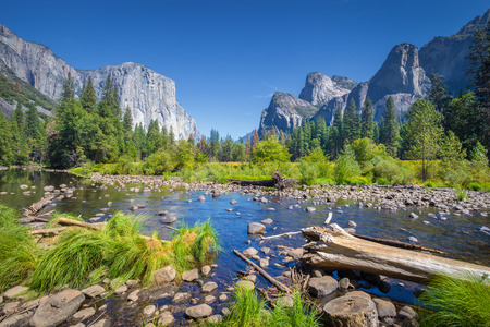Classic view of scenic Yosemite Valley with famous El Capitan rock climbing summit and idyllic Merced river on a sunny day with blue sky and clouds in summer, Yosemite National Park, California, USA Stock Photo