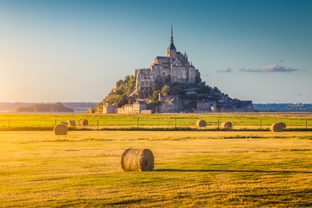 Beautiful view of famous historic Le Mont Saint-Michel in golden evening light at sunset in summer with hay bales on fields with retro vintage Instagram style pastel filter effect, Normandy, France
