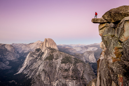 A fearless male hiker is standing on an overhanging rock at Glacier Point enjoying the breathtaking view towards famous Half Dome in beautiful post sunset twilight in summer, Yosemite National Park, California Archivio Fotografico
