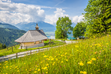 kitzsteinhorn: Panoramic view of beautiful scenery in the Alps with chapel and green meadows full of blooming flowers on a sunny day with blue sky and clouds in springtime, Zell am See, Salzburger Land, Austria Stock Photo