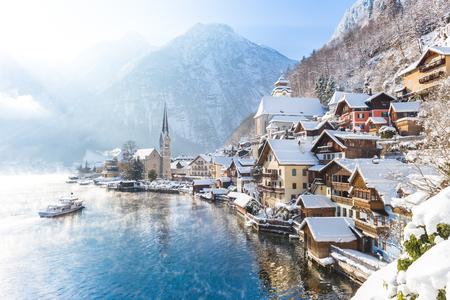 Classic postkaart uitzicht op de beroemde Hallstatt stadje in de Alpen met passagiersschip op een mooie koude zonnige dag met blauwe lucht en de wolken in de winter, in de regio Salzkammergut, Oostenrijk