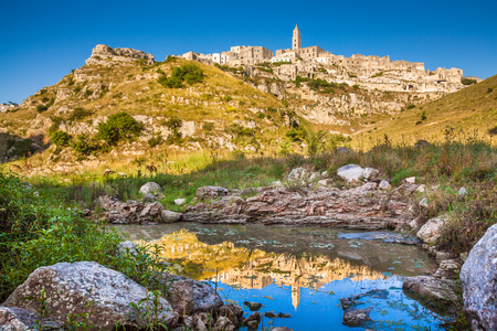 european culture: Classic view of the ancient town of Matera (Sassi di Matera), European Capital of Culture 2019, in beautiful golden morning light with blue sky reflecting in lake, Basilicata, southern Italy