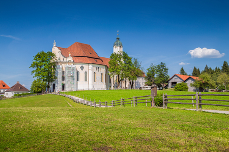 Beautiful view of famous oval rococo Pilgrimage Church of Wies (Wieskirche), a UNESCO World Heritage Site since 1983, with green meadows on a sunny day with blue sky and clouds in Bavaria, Germany