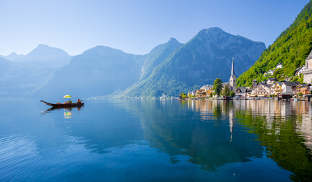 Scenic postcard view of famous Hallstatt lakeside town in the Austrian Alps with traditional wooden Platte boat on a beautiful sunny day with blue sky in summer, Salzkammergut region, Austria