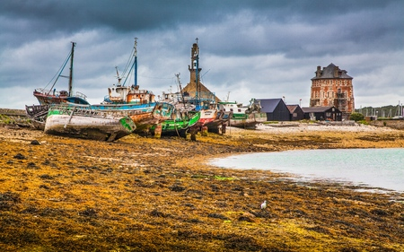Beautiful view of old abandoned shipwrecks lying on a beach with dark dramatic clouds in summer, commune of Camaret-sur-Mer, Bretagne, northwestern France Stock Photo
