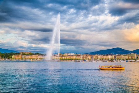 Panoramic view of historic Geneva skyline with famous Jet d'Eau fountain at harbor district in beautiful evening light at sunset with blue sky and clouds in summer, Canton of Geneva, Switzerland