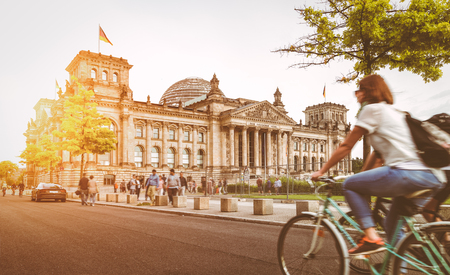 Urban city life with famous Reichstag building in the background in beautiful golden evening light at sunset in summer with retro vintage Instagram style pastel toned filter effect, Berlin, Germany Stock Photo - 75549095