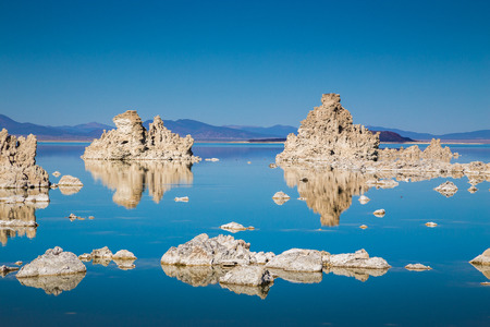 Classic view of fascinating tufa rock formations mirrored on calm water surface of famous Mono Lake on a beautiful sunny day with blue sky in summer, Mono County, California, USA