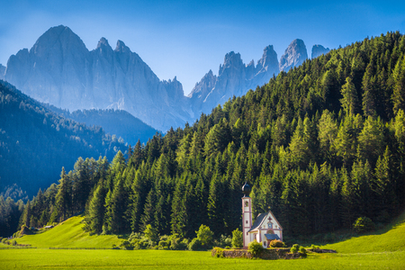 Beautiful view of idyllic mountain scenery with baroque Church of St. Johann of Nepomuk and famous Odle Group in the background on a sunny day with blue sky in the Dolomites in spring, South Tyrol, Italy Stock Photo
