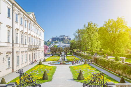 wolfgang: Tourists walking through famous Mirabell Gardens with famous Hohensalzburg Fortress in the background on a sunny day with blue sky and clouds in summer, Salzburg, Salzburger Land, Austria