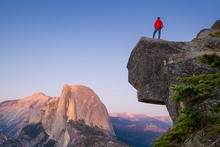 sierra nevada: A fearless hiker is standing on an overhanging rock enjoying the view towards famous Half Dome at Glacier Point overlook in beautiful post sunset twilight, Yosemite National Park, California, USA Stock Photo