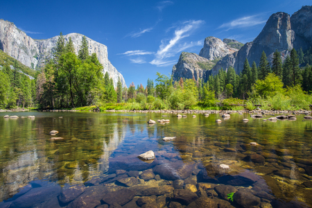 Classic view of scenic Yosemite Valley with famous El Capitan rock climbing summit and idyllic Merced river on a sunny day with blue sky and clouds in summer, Yosemite National Park, California, USA Archivio Fotografico