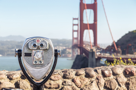 Classic view of coin operated binoculars with famous Golden Gate Bridge in the background on a beautiful sunny day with blue sky and clouds in summer, San Francisco Bay Area, California, USA