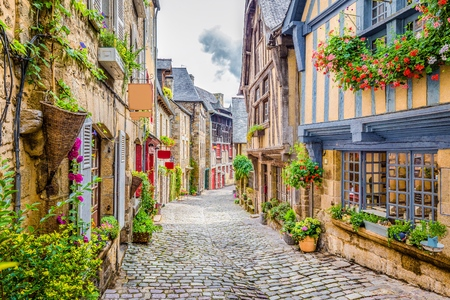 Beautiful view of scenic narrow alley with historic traditional houses and cobbled street in an old town in Europe with blue sky and clouds in summer with retro vintage Instagram grunge filter effect Stock Photo