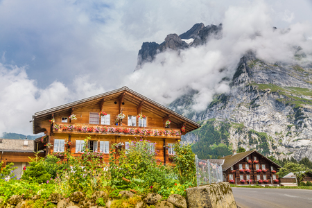Traditional farmhouses in idyllic mountain scenery with high mountain peaks covered in clouds and fog on a beautiful sunny day in summer, Grindelwald, Canton of Bern, Switzerland