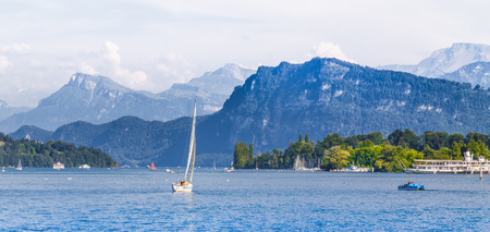 Scenic panoramic view of boats on idyllic Lake Lucerne with alpine mountain scenery in the background on a beautiful sunny day with blue sky and clouds in summer, Lucerne, Switzerland