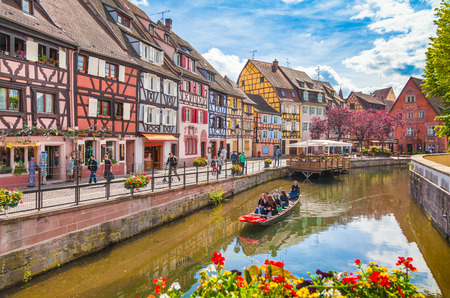 Beautiful view of the historic town of Colmar, also known as Little Venice, with tourists taking a boat ride along traditional colorful houses on idyllic river Lauch in summer, Colmar, Alsace, France Standard-Bild