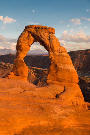 Classic postcard view of famous Delicate Arch, symbol of Utah and a popular scenic tourist attraction, in beautiful golden evening light at sunset in summer, Arches National Park, Moab, Utah, USA Stock Photo