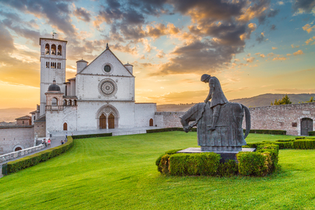 Classic view of famous Basilica of St. Francis of Assisi (Basilica Papale di San Francesco) with statue in beautiful golden evening light with dramatic clouds in the sky at sunset, Assisi, Umbria, Italy Stock Photo